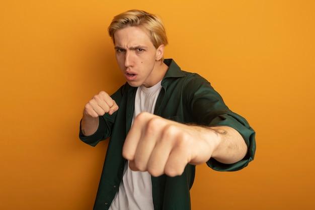 Zelfverzekerde jonge blonde man dragen groene t-shirt staande vechten pose
