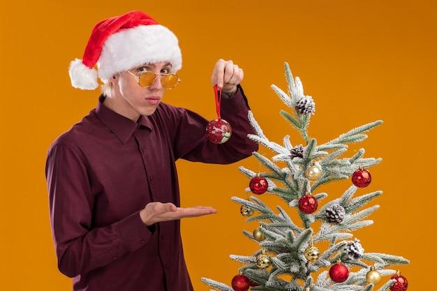 Zelfverzekerde jonge blonde man met kerstmuts en bril staan in profiel te bekijken in de buurt van versierde kerstboom op oranje achtergrond