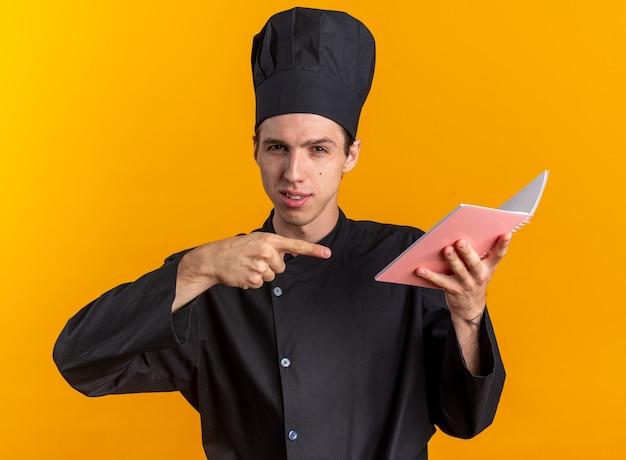 Zelfverzekerde jonge blonde mannelijke kok in chef-kok uniform en pet houden en wijzend op notitieblok kijken naar camera geïsoleerd op oranje muur