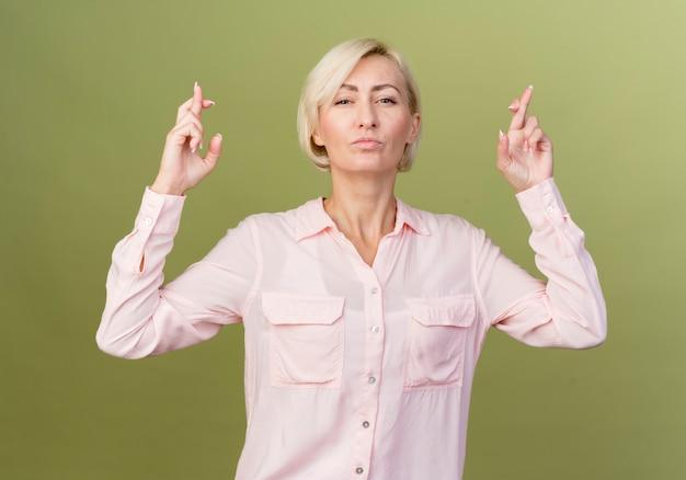 Zelfverzekerde jonge blonde slavische vrouw die vingers kruist
