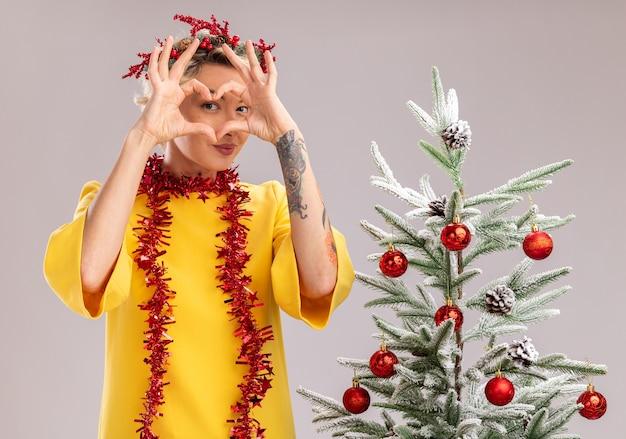 Zelfverzekerde jonge blonde vrouw die de hoofdkroon van kerstmis en klatergoudslinger rond hals draagt die zich dichtbij verfraaide kerstboom bevindt die hartteken voor gezicht doet geïsoleerd op witte muur doet