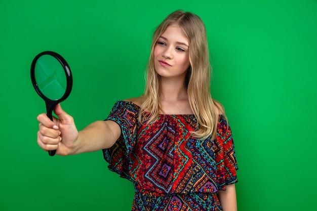 Zelfverzekerde jonge blonde vrouw die vergrootglas vasthoudt en bekijkt