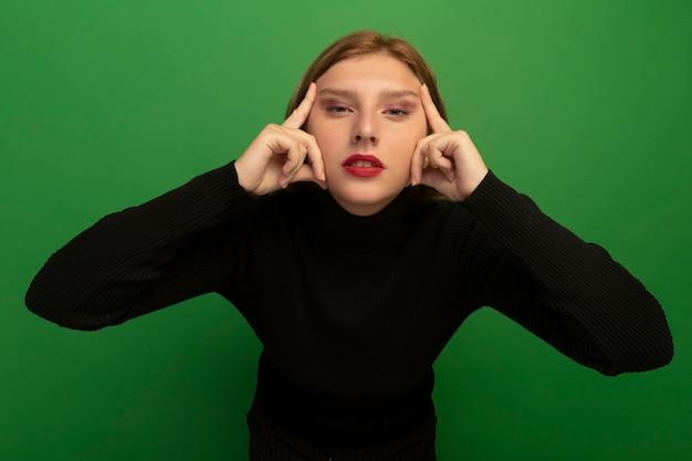 Zelfverzekerde jonge blonde vrouw doet denken gebaar kijken naar voorzijde geïsoleerd op groene muur on