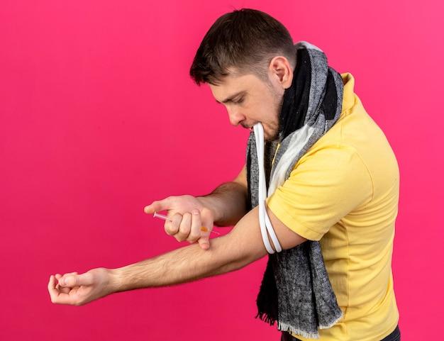 Zelfverzekerde jonge blonde zieke man met sjaal staat zijwaarts trekt harnas met tanden aan en houdt spuit vast die injectie doet aan zichzelf geïsoleerd op roze muur