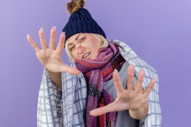 Zelfverzekerde jonge blonde zieke slavische vrouw met medische pleister op neus winter hoed en sjaal dragen
