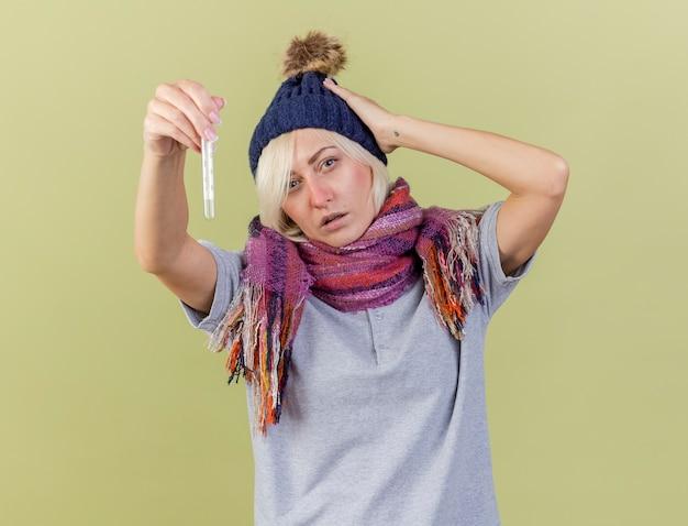Zelfverzekerde jonge blonde zieke slavische vrouw met winter muts en sjaal legt hand op het hoofd en houdt thermometer geïsoleerd op olijfgroene muur met kopie ruimte