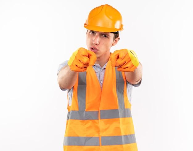 Zelfverzekerde jonge bouwer man in uniform dragen van handschoenen die vuist geïsoleerd op een witte muur