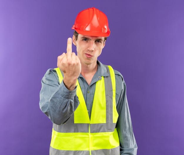 Zelfverzekerde jonge bouwer man in uniform met gebaar geïsoleerd op blauwe muur