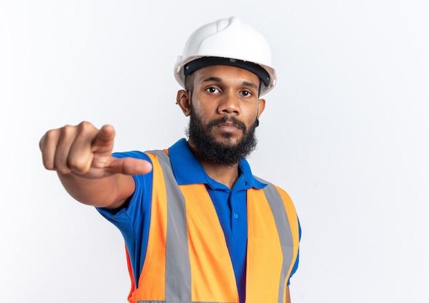 Zelfverzekerde jonge bouwer man in uniform met veiligheidshelm kijkend en wijzend naar voren geïsoleerd op een witte muur met kopieerruimte