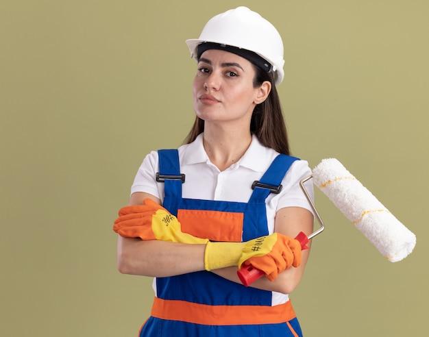 Zelfverzekerde jonge bouwvrouw in uniform en handschoenen die een rolborstel vasthouden en handen kruisen die op olijfgroene muur zijn geïsoleerd