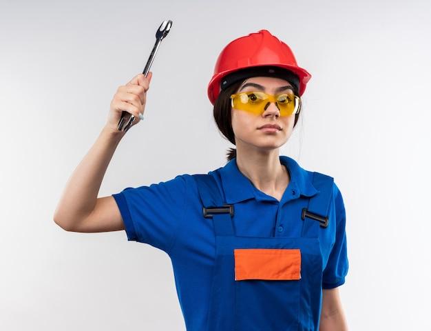 Zelfverzekerde jonge bouwvrouw in uniform met een bril die een steeksleutel opheft