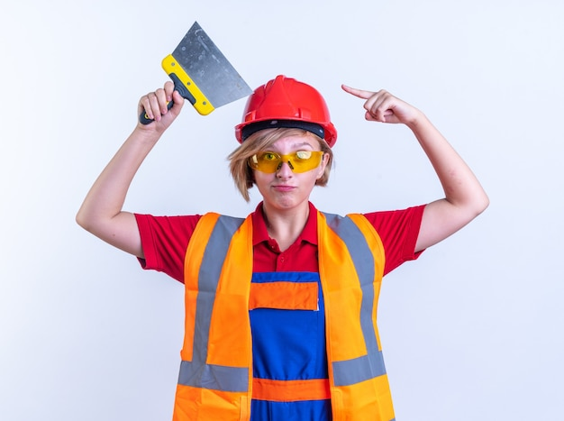 Zelfverzekerde jonge bouwvrouw in uniform met een bril die vasthoudt en wijst naar een plamuurmes dat op een witte muur wordt geïsoleerd