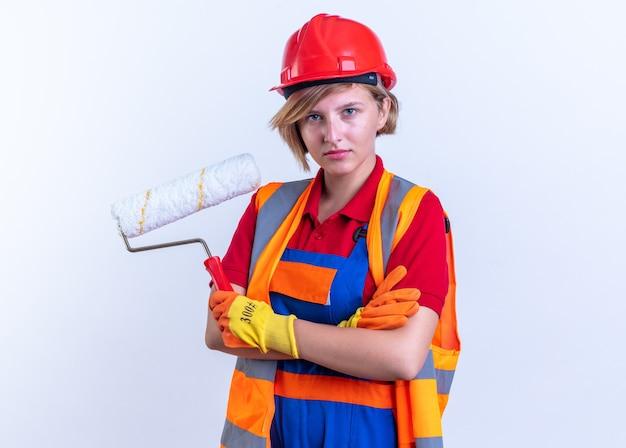 Zelfverzekerde jonge bouwvrouw in uniform met handschoenen met rolborstel die handen kruist geïsoleerd op een witte muur
