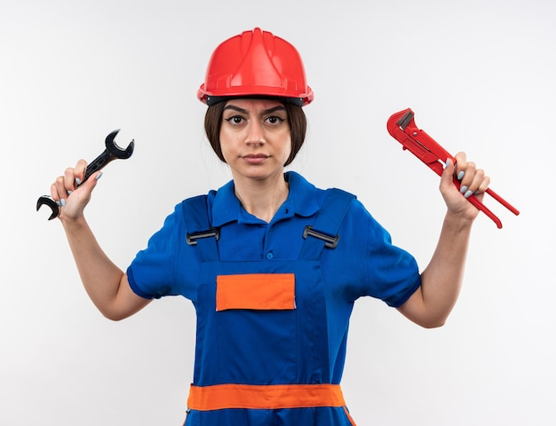 Zelfverzekerde jonge bouwvrouw in uniform met steeksleutel met moersleutel