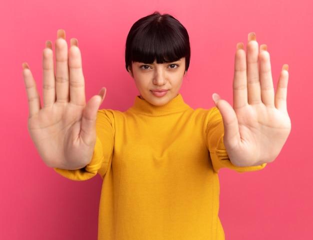 Zelfverzekerde jonge brunette blanke meisjesgebaren stopbord met twee handen geïsoleerd op roze muur met kopieerruimte