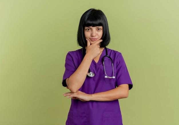 Zelfverzekerde jonge brunette vrouwelijke arts in uniform met stethoscoop legt hand op kin geïsoleerd op olijfgroene achtergrond met kopie ruimte