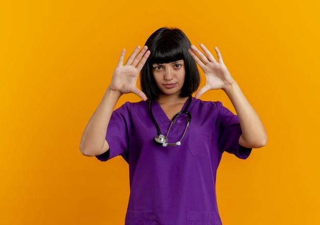 Zelfverzekerde jonge brunette vrouwelijke arts in uniform met stethoscoop staat met opgeheven handen gebaren frame