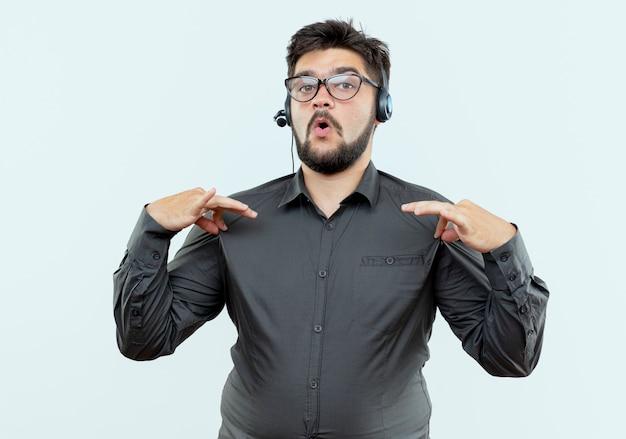 Zelfverzekerde jonge callcentermens met hoofdtelefoon greep die overhemd op witte achtergrond wordt geïsoleerd