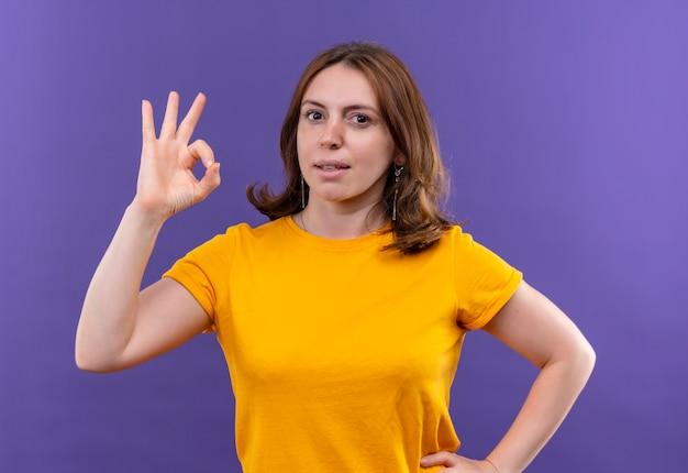 Zelfverzekerde jonge casual vrouw doet ok teken met hand op taille op geïsoleerde paarse ruimte