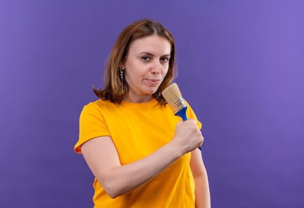 Zelfverzekerde jonge casual vrouw met behulp van kwast als microfoon op geïsoleerde paarse ruimte met kopie ruimte
