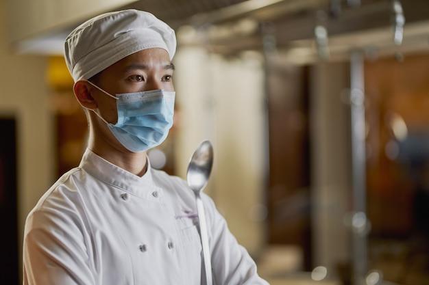 Zelfverzekerde jonge chef-kok poseren in gezichtsmasker