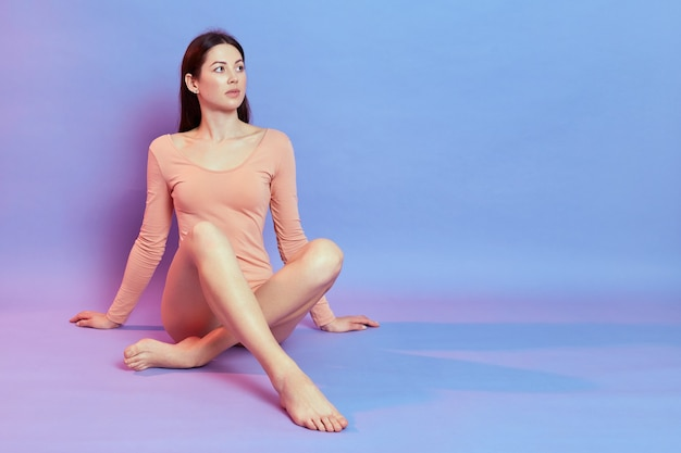 Zelfverzekerde jonge europese dame met slank perfect lichaam zittend op de vloer en leunen op de handpalmen, wegkijkend, vrouw met beige bodysuit geïsoleerd over blauwe muur met roze neonlicht.