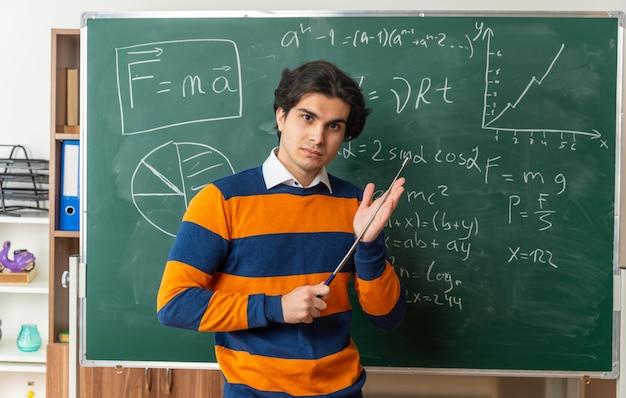 Zelfverzekerde jonge geometrieleraar die voor het schoolbord in de klas staat met de aanwijzer die de hand aanraakt en naar de voorkant kijkt
