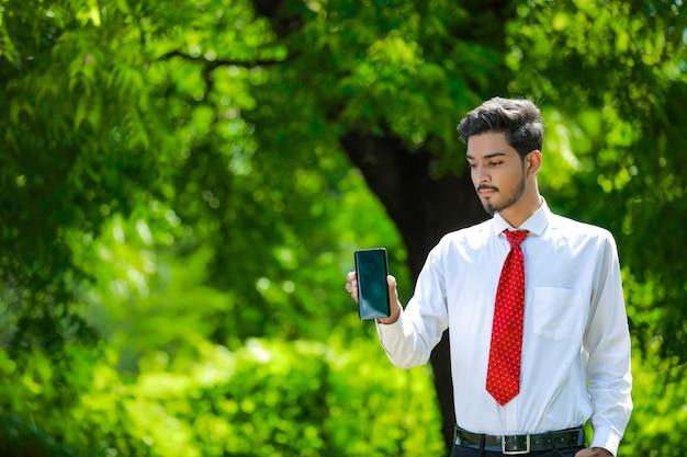 Zelfverzekerde jonge indiase man met zijn slimme telefoon