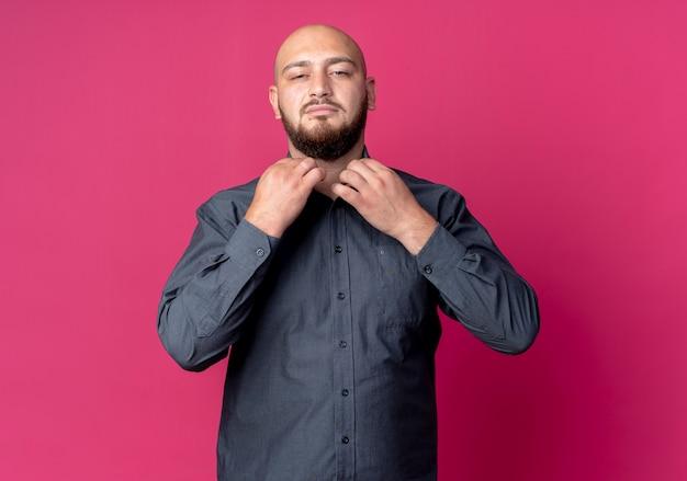 Zelfverzekerde jonge kale call center man grijpen kraag van zijn shirt geïsoleerd op karmozijnrood met kopie ruimte