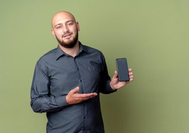 Zelfverzekerde jonge kale callcentermens die bedrijf toont en met hand wijst op mobiele telefoon die op olijfgroen met exemplaarruimte wordt geïsoleerd