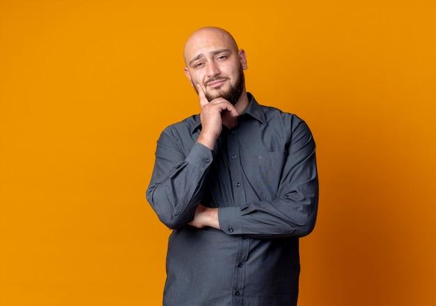 Zelfverzekerde jonge kale callcentermens die hand op kin zet die geïsoleerd op oranje met exemplaarruimte kijkt Gratis Foto