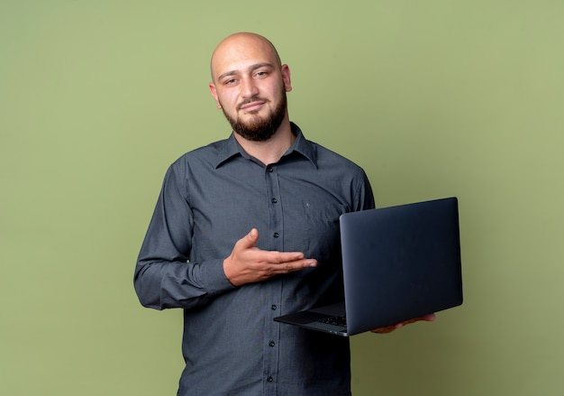 Zelfverzekerde jonge kale callcentermens houden en met hand wijzen op laptop die op olijfgroen met exemplaarruimte wordt geïsoleerd