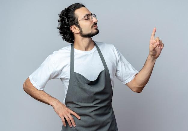 Zelfverzekerde jonge kaukasische mannelijke kapper bril en golvende haarband in uniform kijken kant verhogen vinger met hand op taille geïsoleerd op witte achtergrond