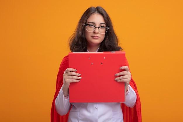 Zelfverzekerde jonge kaukasische superheld meisje in rode cape dragen dokter uniform en stethoscoop met bril met map geïsoleerd op oranje muur met kopie ruimte