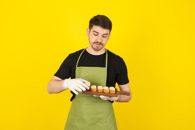 Zelfverzekerde jonge kerel die cakeplakken van stapel op geel neemt.