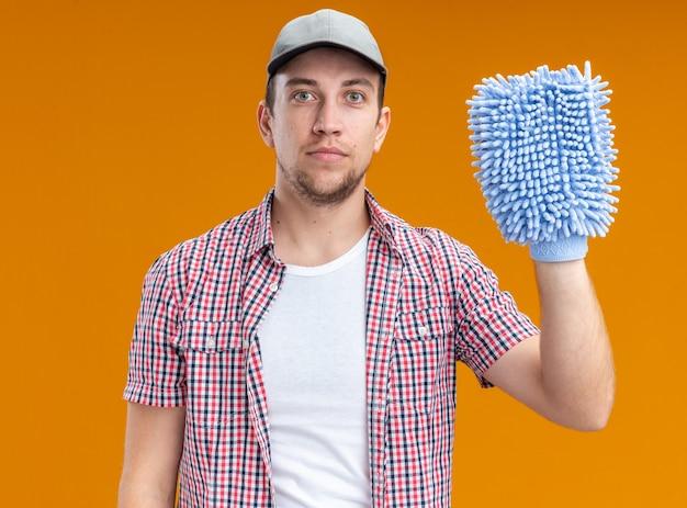 Zelfverzekerde jonge kerel die een dop draagt met een schoonmaakdoek geïsoleerd op een oranje muur