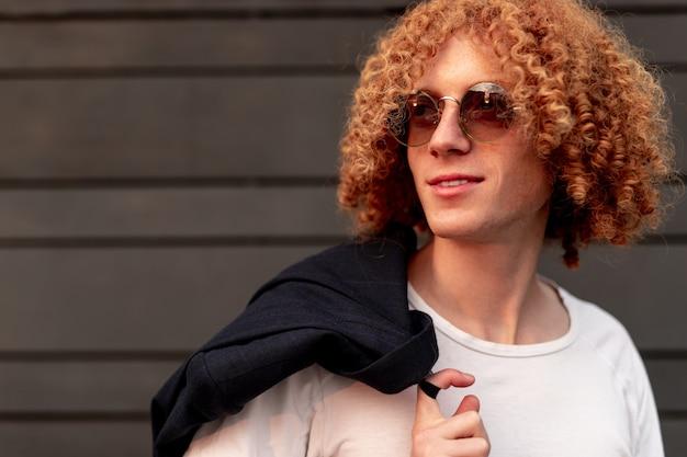 Zelfverzekerde jonge kerel met rood krulhaar in wit t-shirt en zonnebril die op straat met jasje over schouder staat en wegkijkt