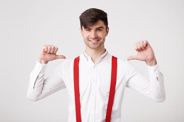 Zelfverzekerde jonge kerel ziet er gelukkig uit terwijl hij met de duim naar zichzelf wijst, voelt zich een winnaar