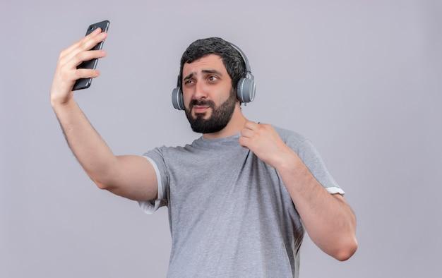 Zelfverzekerde jonge knappe blanke man met koptelefoon zijn shirt vast te houden en selfie te nemen geïsoleerd op wit met kopie ruimte