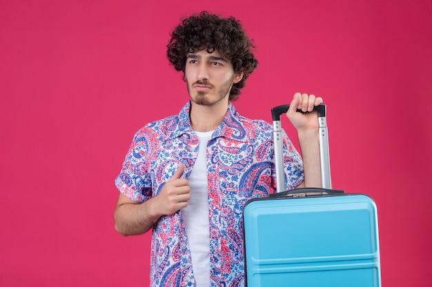 Zelfverzekerde jonge knappe gekrulde reiziger man met koffer en hand op zijn shirt zetten op geïsoleerde roze ruimte met kopie ruimte