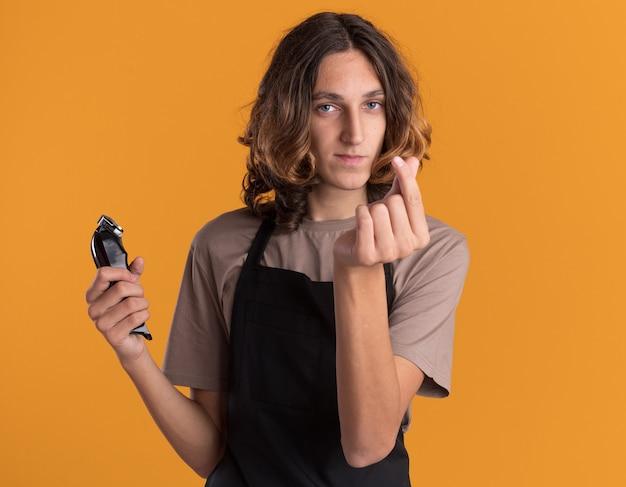 Zelfverzekerde jonge knappe kapper die een uniform draagt met tondeuses die geldgebaar doen