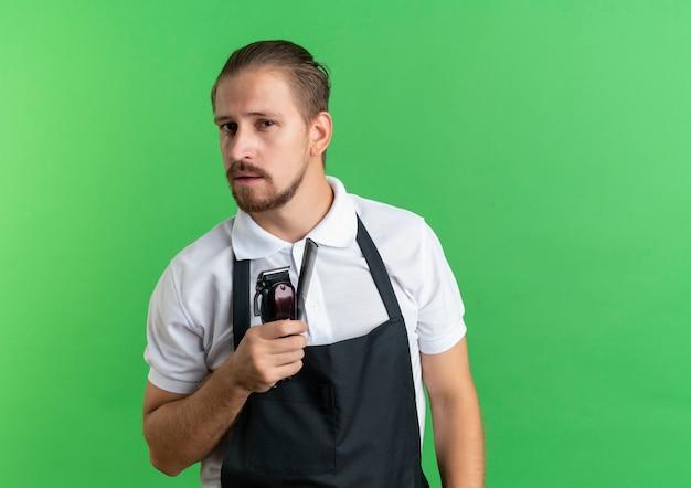 Zelfverzekerde jonge knappe kapper die uniforme holdingskam en tondeuses draagt die op groen met exemplaarruimte wordt geïsoleerd