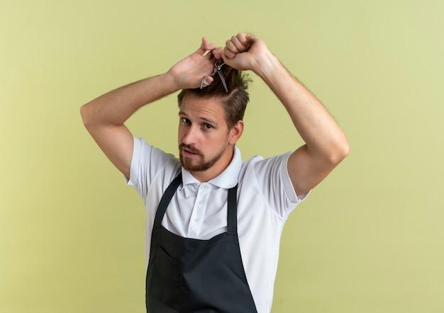 Zelfverzekerde jonge knappe kapper die zijn haar met een schaar knipt die op olijfgroen met exemplaarruimte wordt geïsoleerd