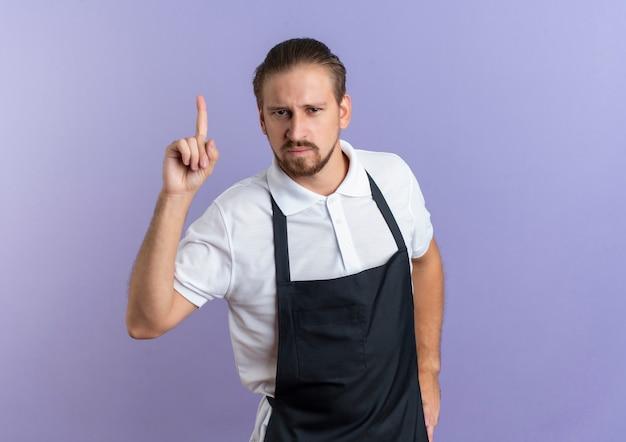 Zelfverzekerde jonge knappe kapper dragen uniform hand op taille zetten en omhoog geïsoleerd op paars met kopie ruimte