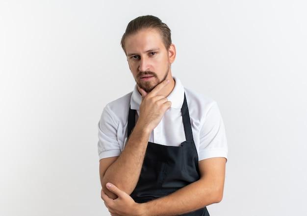 Zelfverzekerde jonge knappe kapper dragen uniform hand op zijn kin en een andere op zijn elleboog geïsoleerd op wit met kopie ruimte te zetten