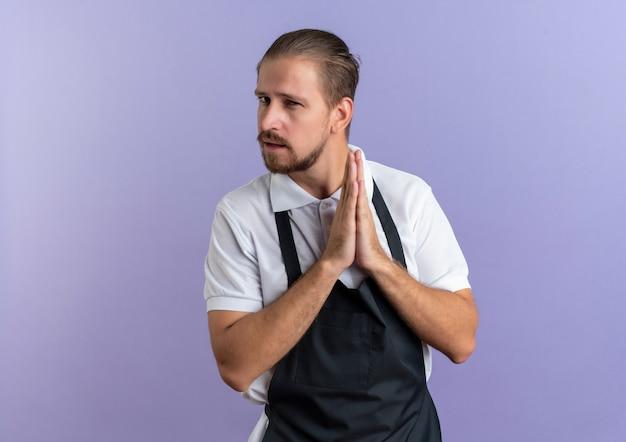 Zelfverzekerde jonge knappe kapper dragen uniform handen bij elkaar houden geïsoleerd op paars met kopie ruimte