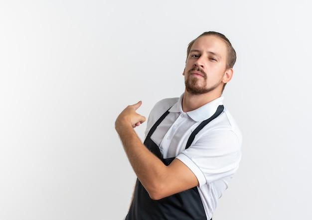 Zelfverzekerde jonge knappe kapper dragen uniform wijzend achter geïsoleerd op wit met kopie ruimte
