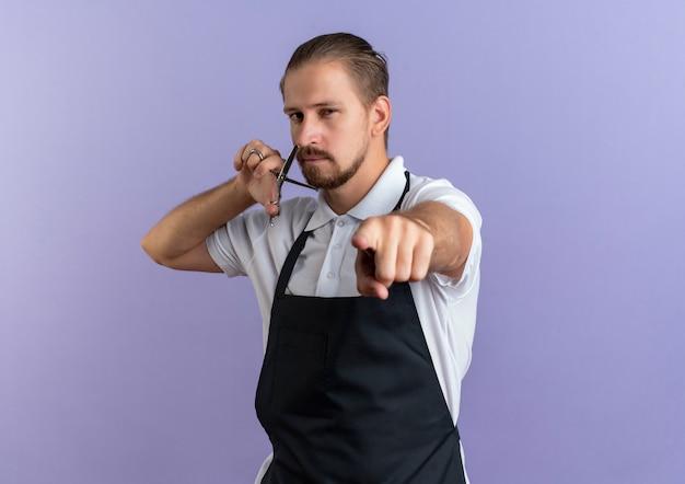 Zelfverzekerde jonge knappe kapper uniforme bedrijf schaar dragen in de buurt van gezicht en wijzen geïsoleerd op paars met kopie ruimte