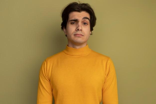 Zelfverzekerde jonge knappe kerel die gele coltrui draagt die op olijfgroene muur wordt geïsoleerd