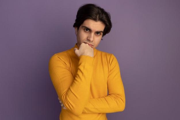 Zelfverzekerde jonge knappe kerel die gele coltrui draagt ?? die vuist op kin zet die op purpere muur wordt geïsoleerd